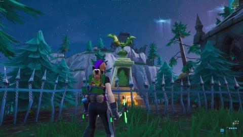 Baila frente una estatua de murciélago, sobre una piscina flotante y una silla de gigante Fortnite