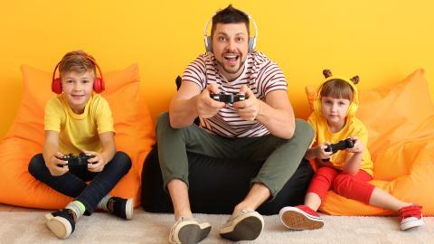 Padre jugando con niños a la consola